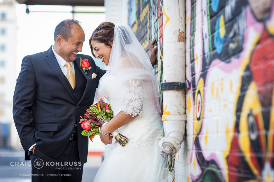 bride and groom laughing in alley